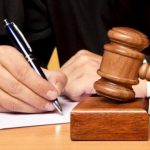 Advogado escrevendo com malhete ao lado