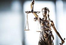 """Foto de escultura """"A Justiça"""" em primeiro plano com fundo desfocado"""