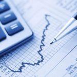 Close-up calculadora e caneta sobre jornal financeiro