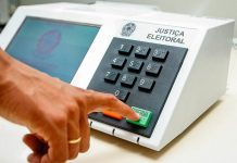 """Close-up de pessoa apertando o botão de """"confirma"""" da urna eletrônica"""
