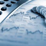 Calculadora e moedas sobre gráficos de índices